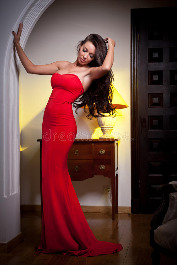 Young beautiful woman wearing a red dress in the old vintage hotel