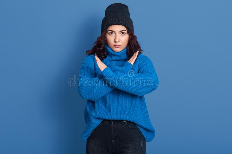 Young beautiful woman wearing warm sweater and hat, winsome angry posing isolated over blue background, doing stop sing with stock image