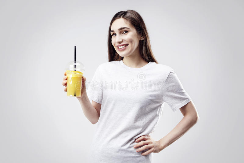 Young beautiful woman wearing white grey t-shirt smiling with orange juice in hand. Portrait isolated on white background stock photo