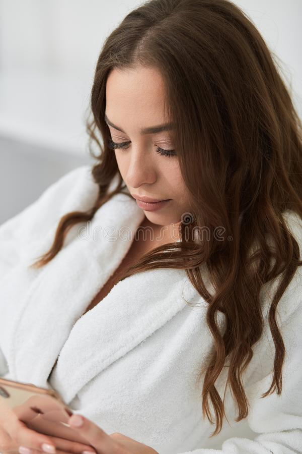 Young beautiful woman in white bathrobe resting at home after taking a shower. stock image