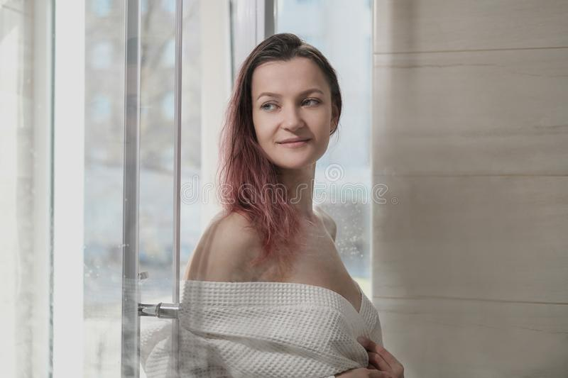 Young beautiful woman in white coat and towel in bathroom. Takes a shower and smiles. Room with a window royalty free stock photo