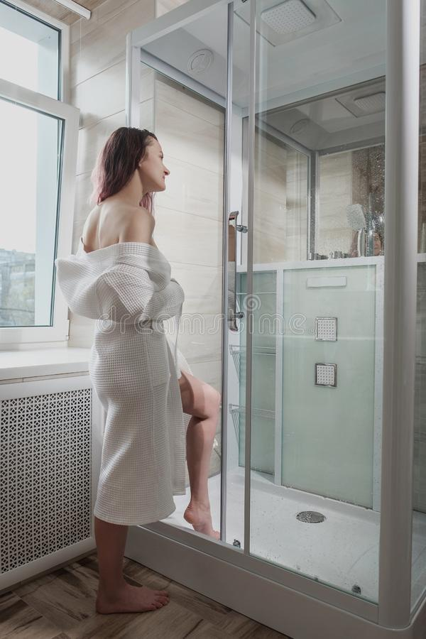 Young beautiful woman in white coat and towel in bathroom. Takes a shower and smiles. Room with a window royalty free stock photography