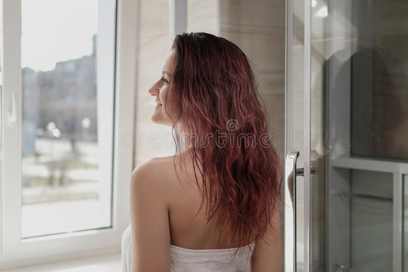 Young beautiful woman in white coat and towel in bathroom. Takes a shower and smiles. Room with a window royalty free stock images