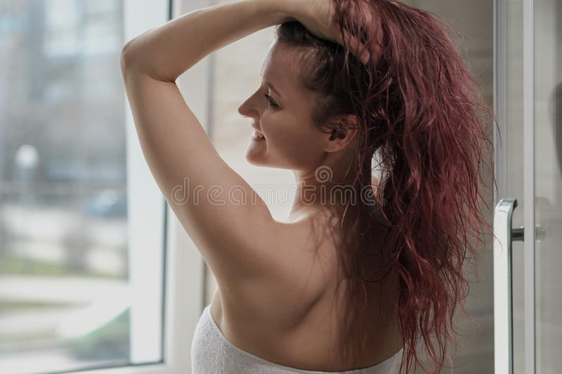 Young beautiful woman in white coat and towel in bathroom. Takes a shower and smiles. Room with a window stock image