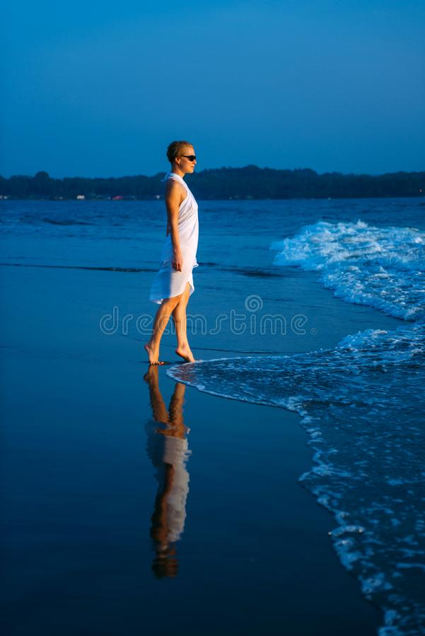 Young and beautiful woman in white dress and sunglasses stands in the surf and looks at blue sea. Figure of girl is reflected. In the water royalty free stock photography