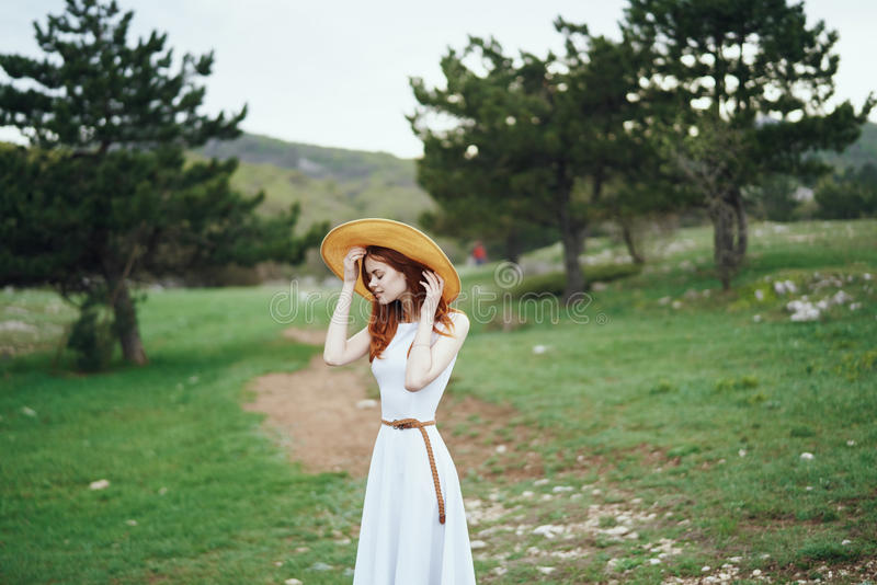 Young beautiful woman in a white dress and wearing a hat in the mountains stock photos