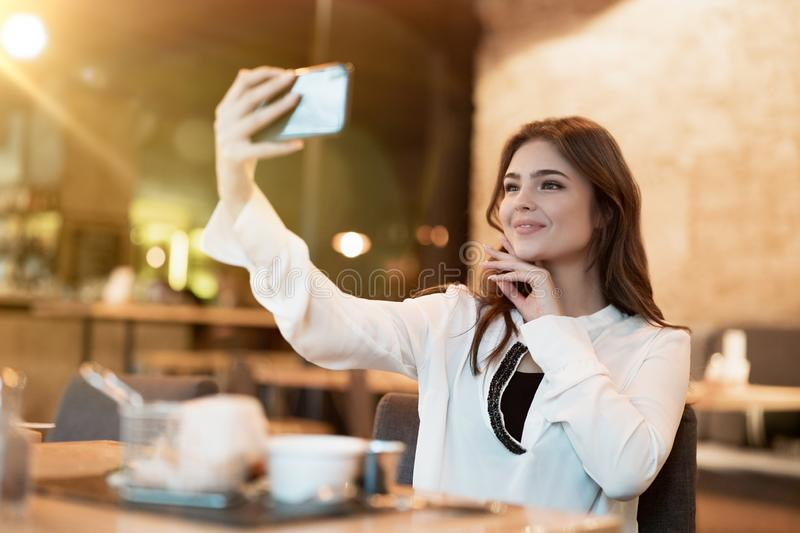 Young beautiful woman in white stylish blouse looks nice while taking selfie before having meat burger with fries for lunch in royalty free stock photo