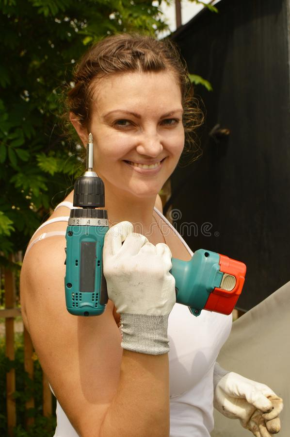 Young beautiful woman in a white t-shirt, holding a screwdriver with gloves. Woman Builder posing outdoors royalty free stock images