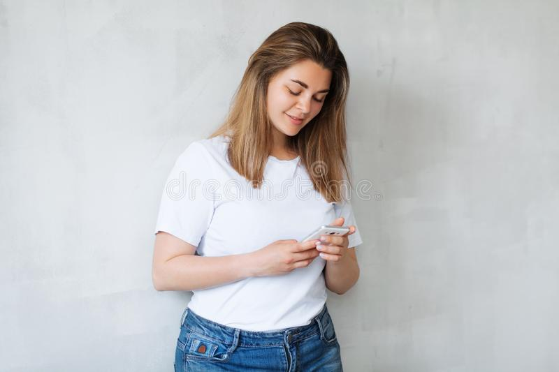 Young beautiful woman in casual style clothes with smartphone stock image