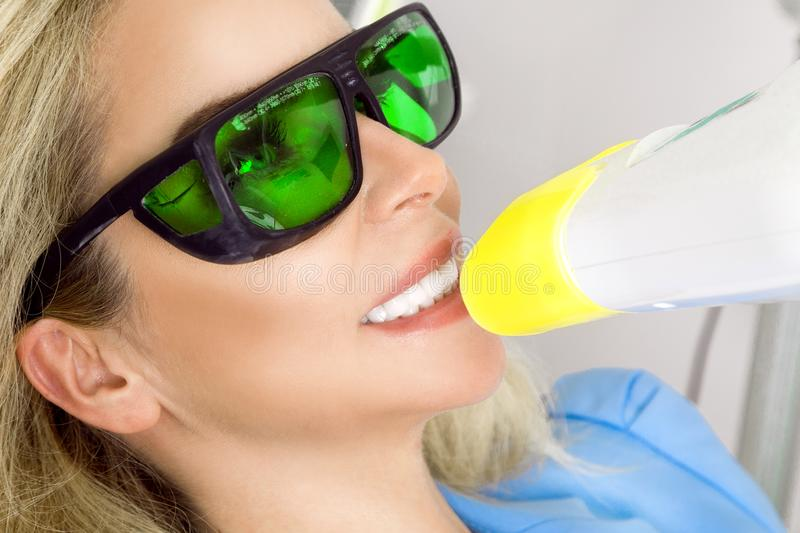 Young beautiful woman with beautiful white teeth sitting on a dental chair. The dentist cures her teeth royalty free stock photos