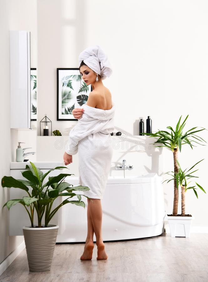 Young beautiful woman with white towel on head standing near bathtub wearing bathrobe in modern bathroom stock photo
