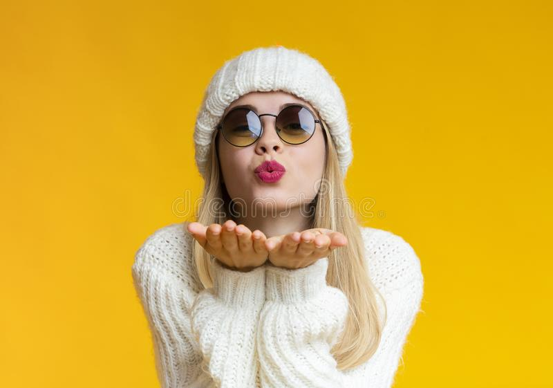 Young beautiful woman in winter hat and sunglasses blowing kiss stock images
