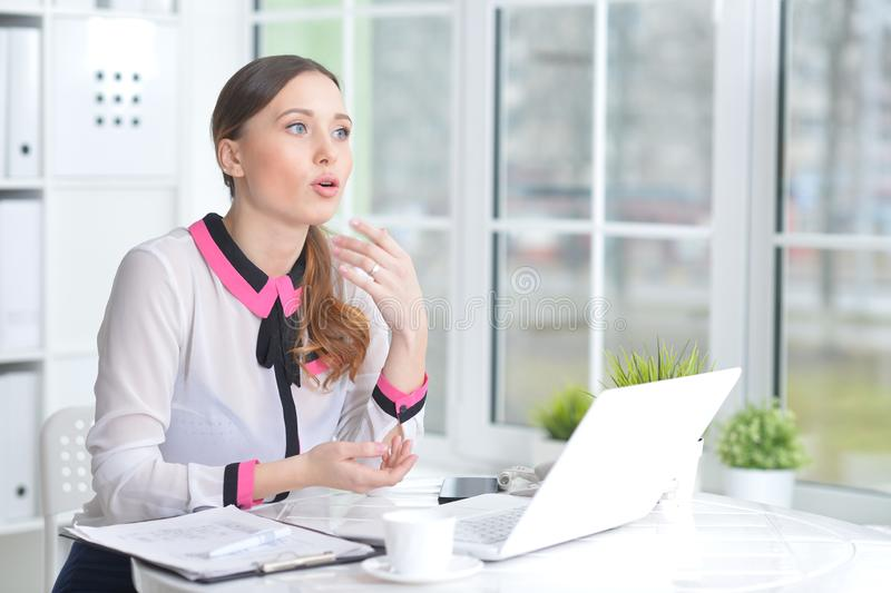 Portrait of young beautiful woman working with laptop in modern office. Young beautiful woman working with laptop in modern office stock image