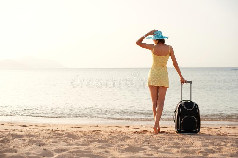 Young beautiful woman in yellow dress and hat with large suitcase on tropical beach. Girl look on sea stock photos