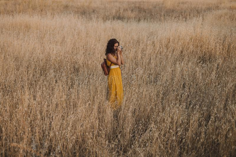 Young beautiful woman in yellow dress taking pictures with an old vintage camera. Countryside. Outdoors. Travel concept stock photos