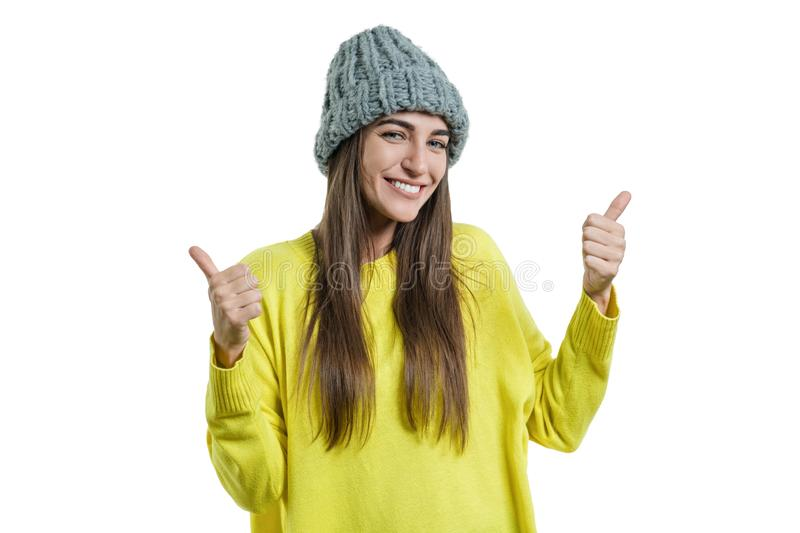 Young beautiful woman in yellow sweater and gray big loop knitted beanie hat, showing sign ok thumbs up, looking at the camera on royalty free stock image