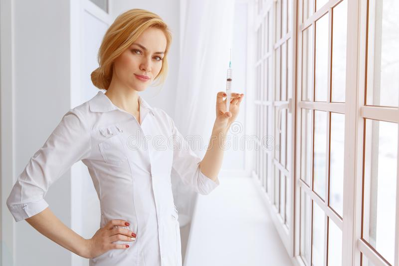 Young beautiful women doctor with syringe. Medicine and health c stock photography