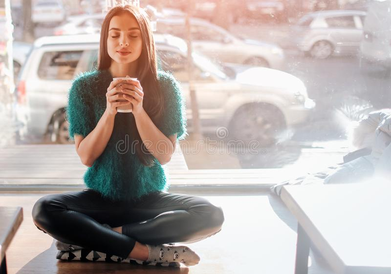 Young beautiful woman drinking coffee at cafe bar. Female model in the morning at restaurant royalty free stock photo