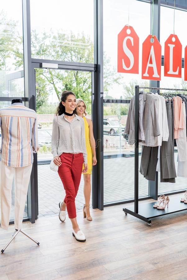 Young beautiful women entering. Clothes store stock photography