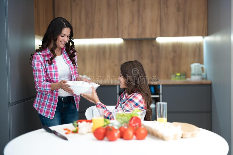 Young beautiful woman and her cute daughter cooking breakfast in the kitchen wearing family look royalty free stock photography