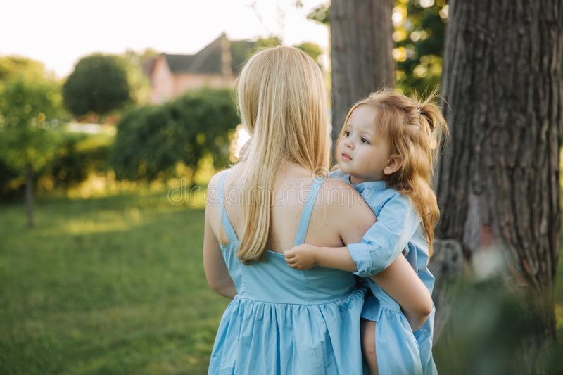 Young beautiful woman with her little cute daughter. Young daughter hugs mother in summer park stock photography