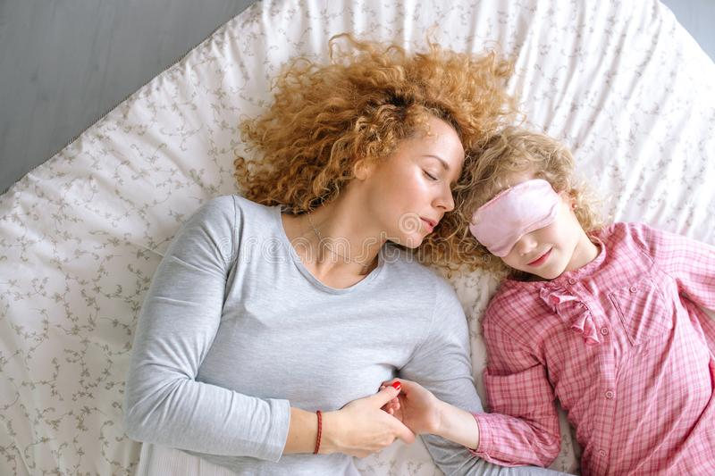 Young beautiful woman holding her child`s hand and sleeping next to her stock photography
