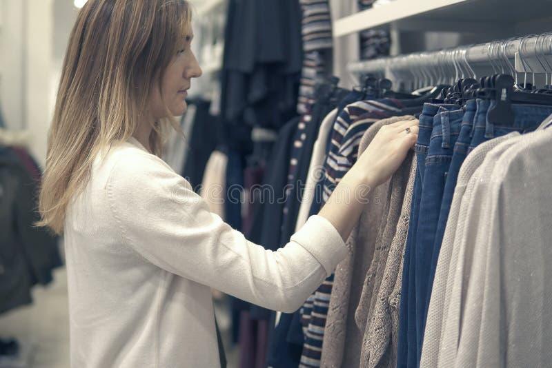 Young beautiful women shopping in fashion mall, choosing new clothes stock image