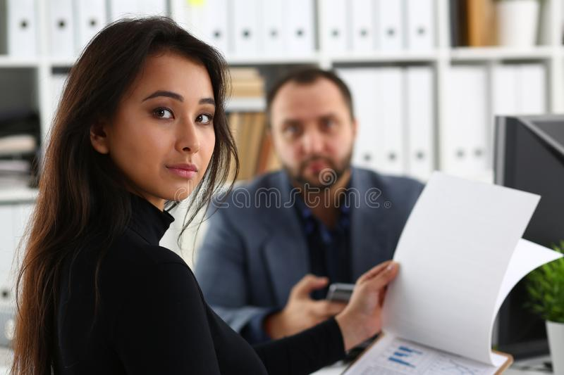Young beautiful woman sit on chair at table in office in cabinet of her boss hold binder in arms royalty free stock images