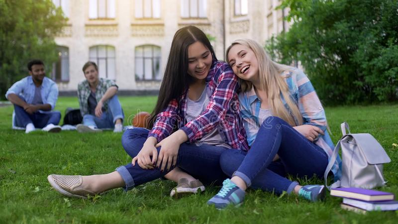 Young beautiful women sitting on lawn near college, laughing and gossiping. Stock photo royalty free stock photos