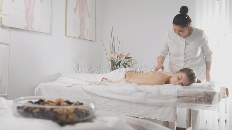 Young beautiful woman in spa receiving procedure of tibetan medicine stock image