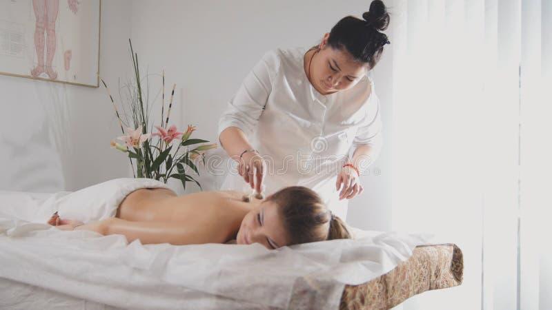 Young beautiful woman in spa receiving procedure of tibetan medicine royalty free stock photos