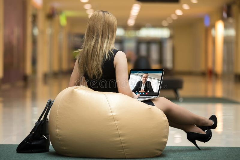 Young beautiful woman chatting with handsome man via video chat. Young beautiful women wearing short dress, high heels sitting on beanbag, chatting with stock photography