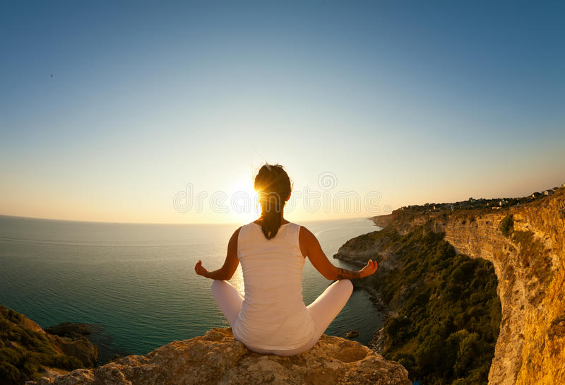 Young beautiful yoga woman meditating in lotus pose on the precipice of a cliff overlooking the sea. royalty free stock image