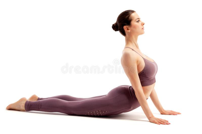 Young beautiful yoga woman is posing in studio on white royalty free stock photography