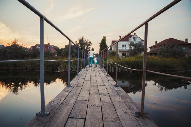 Young beautuful family at the bridge, father, mother and kids are going back home from outside.  royalty free stock images