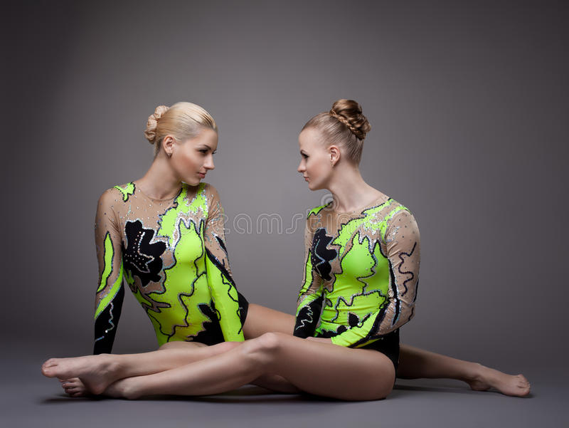 Young beauty acrobats sit and look aggressive stock image