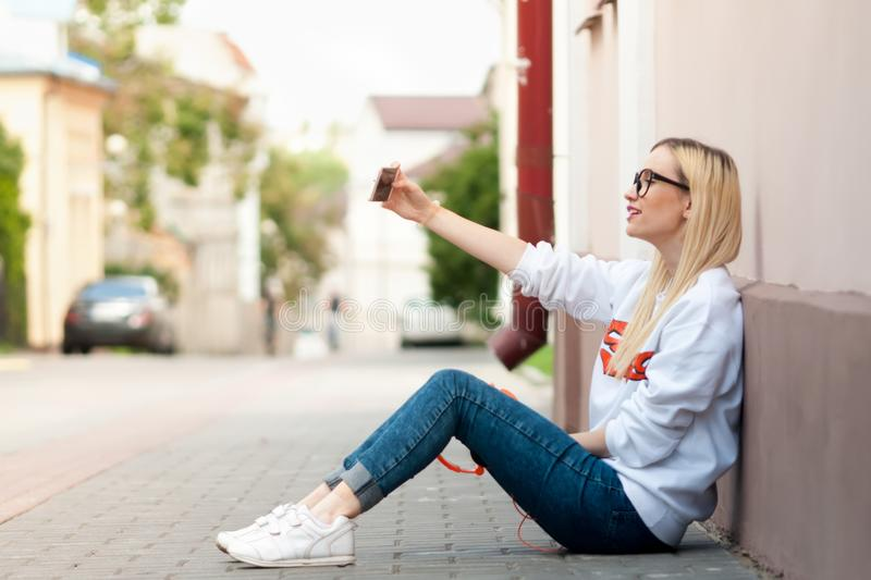 Young beauty american girl make selfie. Fashion model, pretty girl, outdoor portrait, hipster, lips red, make up, beauty street photo, outdoors royalty free stock photography
