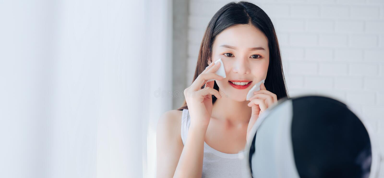 Young Beauty Asian Woman Cleaning Face with Cotton Her Looking at Mirror stock photo