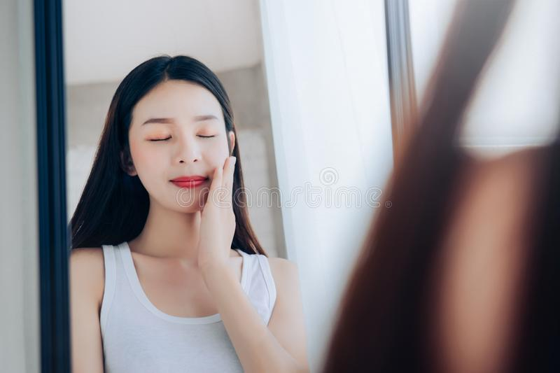 Young Beauty Asian Woman Looking at Mirror Check Clear Face Skincare. And Smile Morning in White Bedroom stock photography