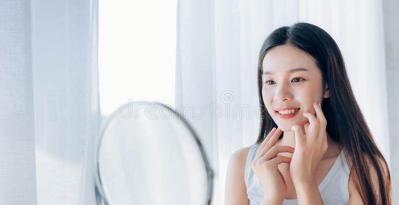 Young Beauty Asian Woman Looking at Mirror Check Clear Face stock photos