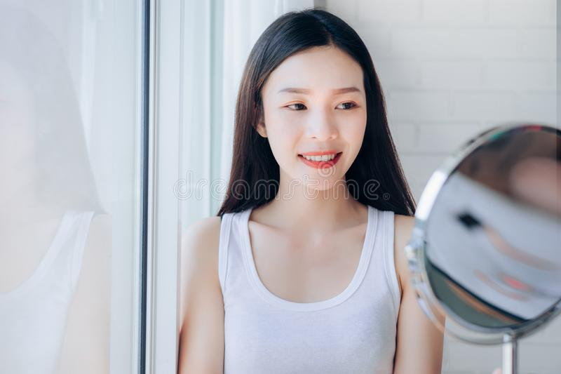 Young Beauty Asian Woman Looking at Mirror Check Clear Face. Skincare and Smile Morning in White Bedroom stock photo
