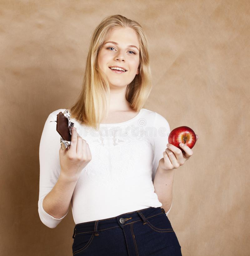 Young beauty blond teenage girl eating chocolate smiling, choice between sweet and apple. Young beauty blond teenage girl eating chocolate smiling, choice stock images