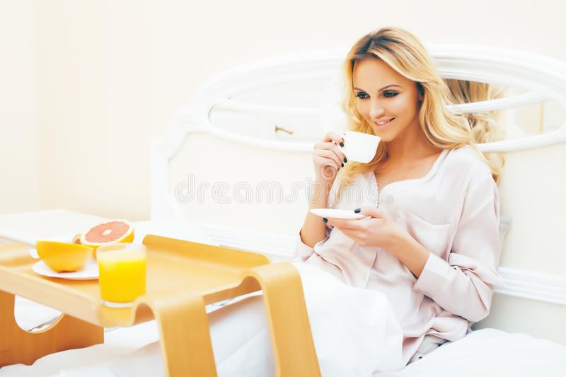 Young beauty blond woman having breakfast in bed early sunny morning, princess house interior room, healthy lifestyle. Concept closeup stock image