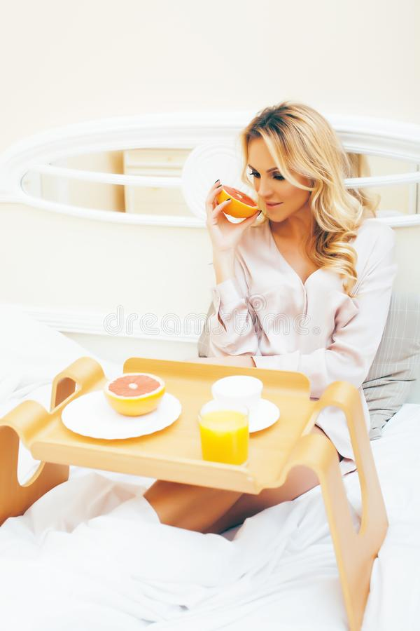 Young beauty blond woman having breakfast in bed early sunny morning, princess house interior room, healthy lifestyle. Concept closeup stock images