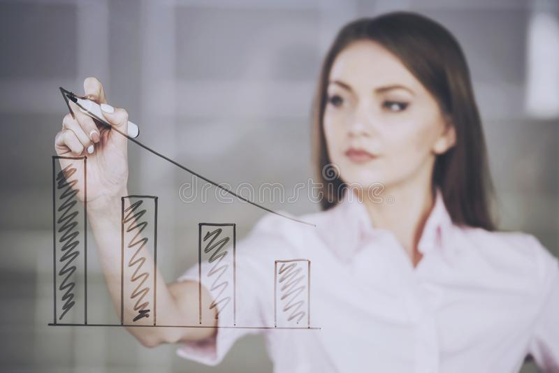 Young beauty businesswoman drawing a graph on glass screen in office royalty free stock photos