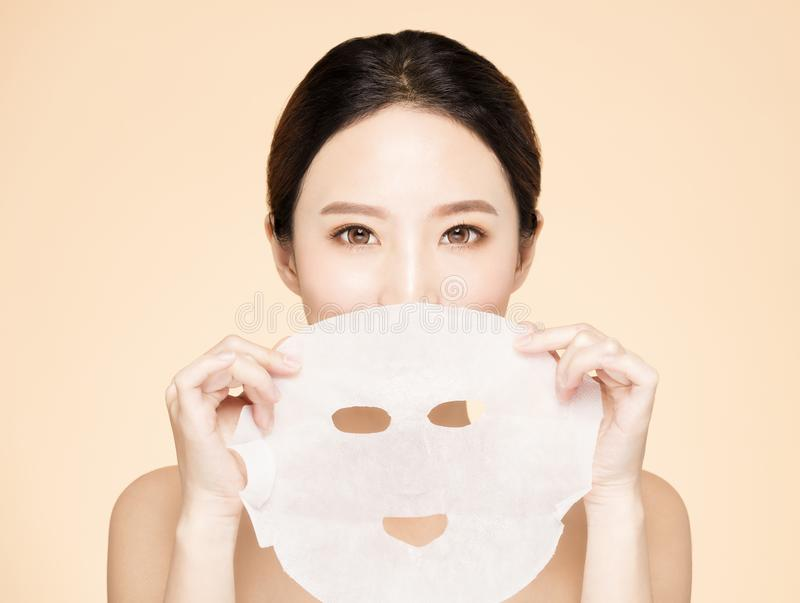 Young beauty face and facial mask stock image