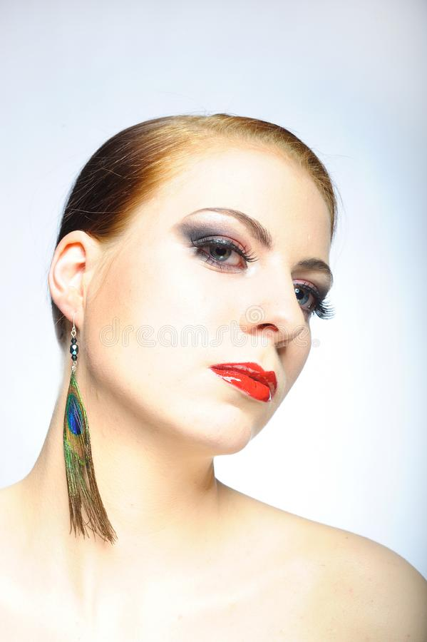 Young beauty female face with red shiny lips royalty free stock photography