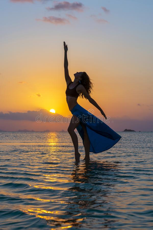 Young beauty girl dancing at tropical beach on sea water at paradise island at sunset. Summer concept. Holiday travel royalty free stock image