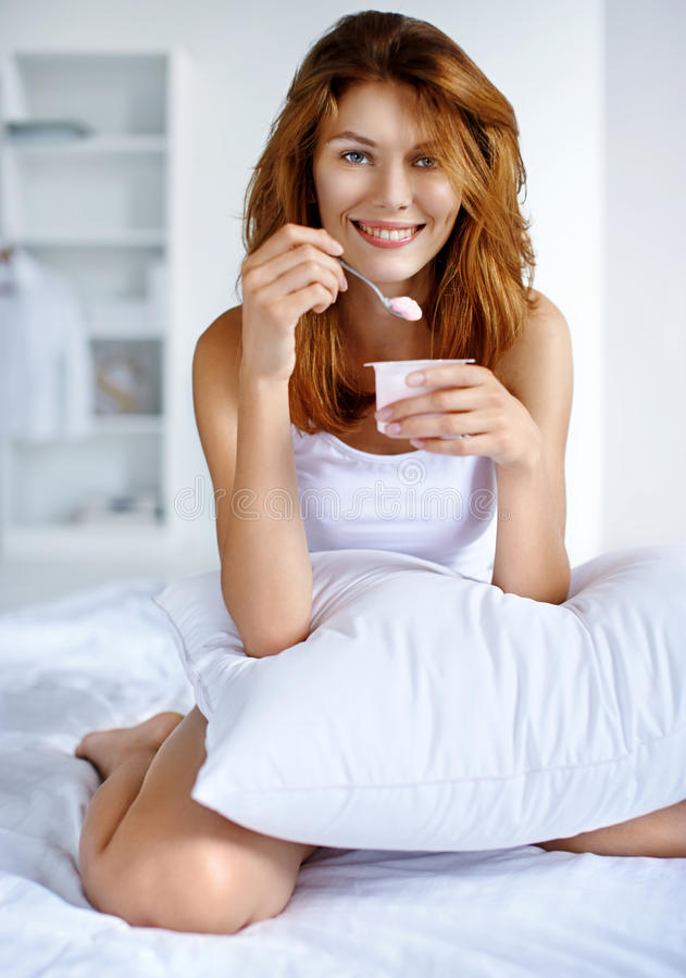Young beauty girl on diet eating. Morning breakfast meal woman eating healthy yogurt while sitting on the bed royalty free stock image