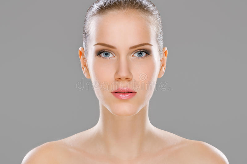 Young beauty isolated on gray stock image